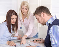 Teamwork at office with three young businesspeople. Stock Photography