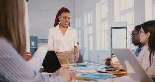 Teamwork på den sunda arbetsplatsen Härlig ung svart kvinnlig lagledare som talar till lyckliga anställda som frambringar idéer arkivfilmer