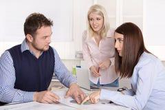 Teamwork på kontoret med tre unga businesspeople. arkivfoto