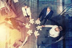Teamwork of partners. Concept of integration and startup with puzzle pieces. Businessmen working together to build a big puzzle. Concept of teamwork, partnership Stock Photo
