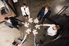 Teamwork of partners. Concept of integration and startup with puzzle pieces. Businessmen working together to build a big puzzle. Concept of teamwork, partnership Stock Images