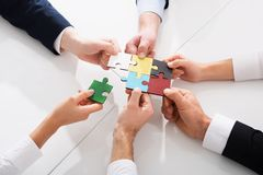 Teamwork of partners. Concept of integration and startup with puzzle pieces. Businessmen working together to build a colored puzzle. Concept of teamwork stock images