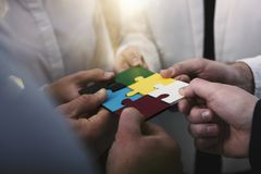 Teamwork of partners. Concept of integration and startup with puzzle pieces. Businessmen working together to build a colored puzzle. Concept of teamwork stock photos
