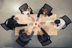 Teamwork of partners. Concept of integration and startup with puzzle pieces. Businessmen working together to build a puzzle. Concept of teamwork, partnership royalty free stock photos