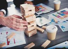 Teamwork of partners. Concept of integration and startup with a small construction of wooden toy. Businessmen working together to build a small construction of Royalty Free Stock Photography