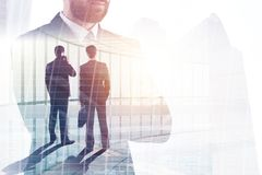Teamwork and partnership concept. Businessmen in abstract office interior with city view. Teamwork and partnership concept. Double exposure Royalty Free Stock Photography