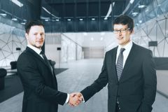 Teamwork and partnership concept. Handsome cheerful european businessmen shaking hands in blurry office interior. Teamwork and partnership concept. 3D Rendeirng Royalty Free Stock Photos