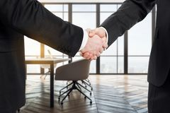 Teamwork and partnership concept. Unrecognizable businessmen shaking hands in modern meeting room interior with city view and daylight. Teamwork and partnership royalty free stock images