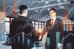 Teamwork, partnership and stock concept. Side view of attractive european businessmen shaking hands in modern blurry office with forex chart. Teamwork royalty free stock photo