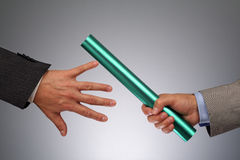 Teamwork passing the baton. Partnership or teamwork concept two businessmen handing over a baton stock photography