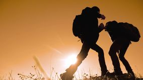 Teamwork people tourists business travel trip lends a helping hand. two men with backpacks hiking help each other. Silhouette in mountains with sunlight. slow stock video footage
