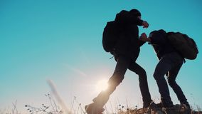 Teamwork people tourists business travel trip lends a helping hand. two men with backpacks hiking help each other. Teamwork people tourists business travel trip stock video footage