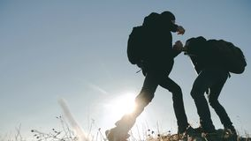 Teamwork people tourists business travel trip lends a helping hand. Two men with backpacks hiking help each other. Teamwork people tourists business travel trip stock footage