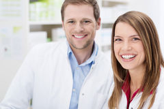 Teamwork at the pharmacy. With a happy young male and female pharmacist smiling happily at the camera, close up of their faces Stock Photography
