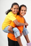 Teamwork piggy back ride by two happy young girls. Two happy young ethnic school girls, wearing orange and yellow t-shirts, giving each other a piggy back ride Royalty Free Stock Image