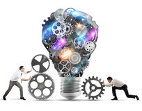 Teamwork powering an idea. Business team push gears towards a great light bulb. build an idea concept stock photo