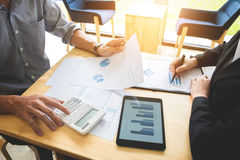 Teamwork process, Two business colleague meeting to discussing t. He new project business strategy plan with digital tablet and calculator. Briefing royalty free stock images