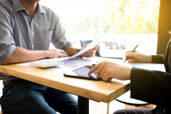 Teamwork process, Two business colleague meeting to discussing t. He new project business strategy plan with using digital tablet and calculator. Briefing royalty free stock image