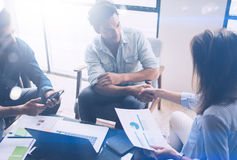 Teamwork process.Young coworkers work with new startup project in office.Analyze document, plans.Modern laptop on wood. Table, papers, documents.Horizontal stock images