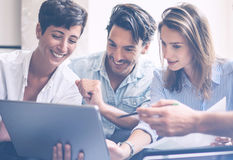 Teamwork process.Young entrepreneur work with new startup project in office.Woman holding touch pad in hands.Horizontal. Blurred, flar Stock Image