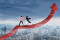 Teamwork pulling arrow upward Stock Photos
