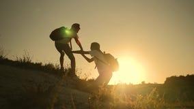 teamwork Schattenbild von den Kindern, die heraus eine Handreichung halten Zwei Jungentouristen auf den Berg Kinderhilfe stock footage