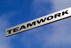 Teamwork sign. Blank aluminium finger sign against blue sky pointing to TEAMWORK stock photo