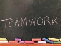Teamwork som ?r skriftlig p? en svart tavla arkivbilder