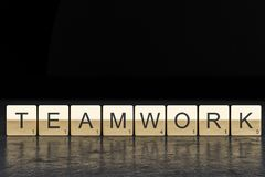 Teamwork spelled from gold scrabble tiles royalty free stock images