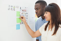 Teamwork standing and taking sticky notes Royalty Free Stock Image