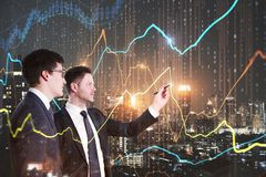 Teamwork and stock concept. Two attractive european businessmen using glowing forex chart on blurry night city background. Teamwork and stock concept. Double royalty free stock photography