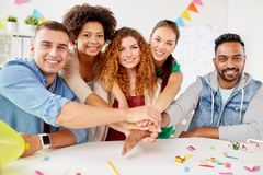 Happy business team at office party holding hands. Teamwork, success and celebration concept - happy business team holding hands together at office corporate Royalty Free Stock Photography