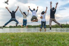 Teamwork success concept with group of jumping friends in the public park. Team work Concept stock photography