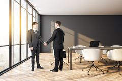 Teamwork and success concept. Happy handsome european businessmen shaking hands in modern conference room interior with city view and daylight. Teamwork and stock image