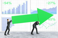 Teamwork and success concept. Two businessmen carrying huge green chart arrow on financial business report background. Teamwork and success concept. 3D Rendering Royalty Free Stock Photos