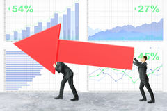 Teamwork and success concept. Two businessmen carrying huge red chart arrow on financial business report background. Teamwork and success concept. 3D Rendering Royalty Free Stock Photo