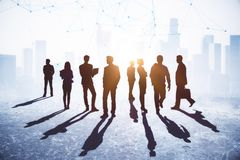 Teamwork, success and employment concept. Crowd of businessmen and women standing on abstract city background with sunlight and shadows. Teamwork, success and stock photos
