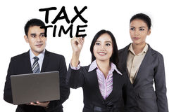Teamwork with tax time. Portrait of businesspeople writes a text of tax time on whiteboard to remind the time for paying tax Royalty Free Stock Photos