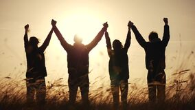 Teamwork. team community hold hands together silhouette at sunset unity. group of people hands. teamwork workers carry
