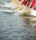 Teamwork. A team of rowers work together as a team to propel their boat forward Stock Image