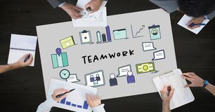 Teamwork text by icons and business people on table. Digital composite of Teamwork text by icons and business people on table Stock Images