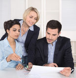 Teamwork between three business people at desk at office. Stock Photos