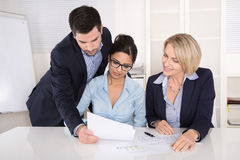 Teamwork between three business people at desk at office. Royalty Free Stock Image