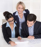 Teamwork between three business people at desk at office. Royalty Free Stock Photos