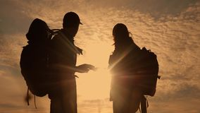 Teamwork tourism navigation concept. happy family hikers silhouette in nature looking in a smartphone navigation path. Man and woman with backpacks silhouette stock video