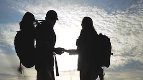 Teamwork tourism navigation concept. happy family hikers silhouette in nature looking in a smartphone navigation path stock video footage