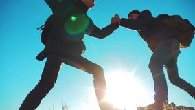 Teamwork tourists business travel trip lends a helping hand. two men with backpacks hiking lifestyle help each other. Silhouette in mountains with sunlight stock footage