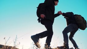 Teamwork tourists business travel trip lends a helping hand. two men lifestyle with backpacks hiking help each other. Teamwork tourists business travel trip stock video footage