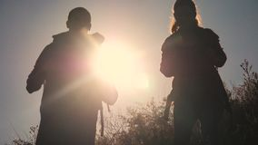 Teamwork tourists travel concept slow motion video. Hiking silhouette happy family couple man and girl go hiking stock video footage