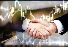 Teamwork and trade concept. Handshake and forex chart on abstract blurry background with laptop. Teamwork and trade concept. Double exposure stock image